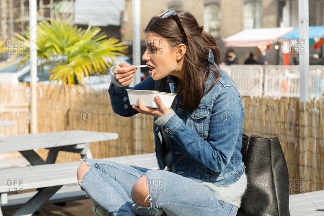 Young women eating takeaway food on picnic bench