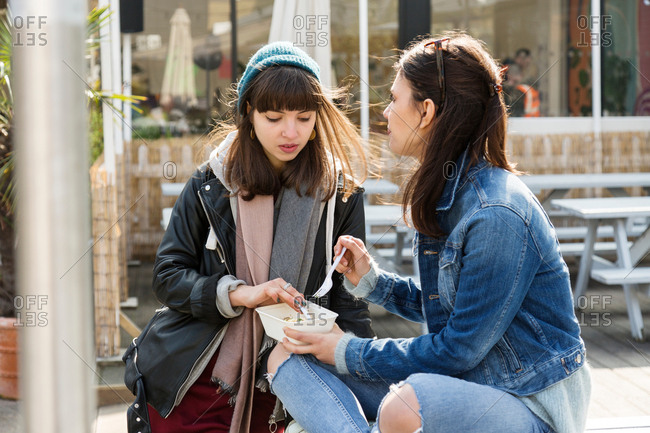 Young women eating takeaway food at picnic bench