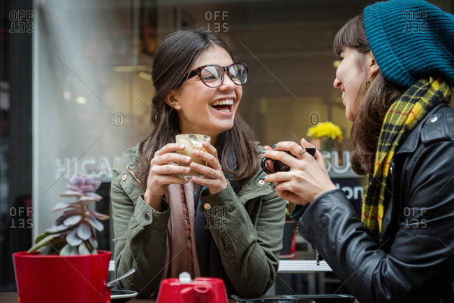 Two young women at sidewalk cafe laughing
