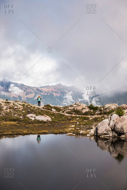 Hiker by lake on Mount Baker, Washington, USA
