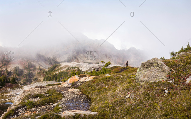 Hiker looking at clouds on mountain peaks, Mount Baker, Washington, USA