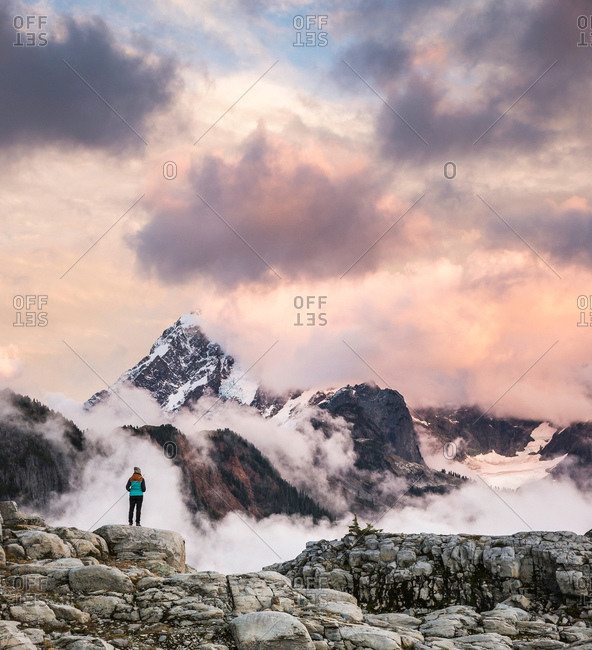 Hiker looking at clouds on snow covered mountains, Mount Baker, Washington, USA