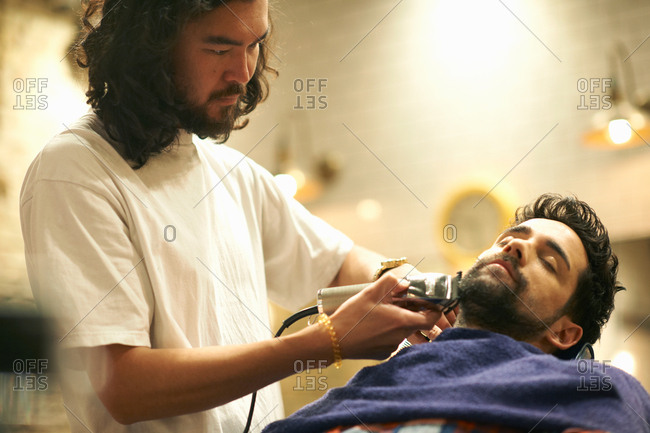 Hairdresser in barbershop shaving customer's beard