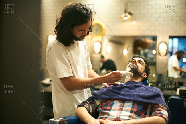 Hairdresser in barbershop giving customer wet shave