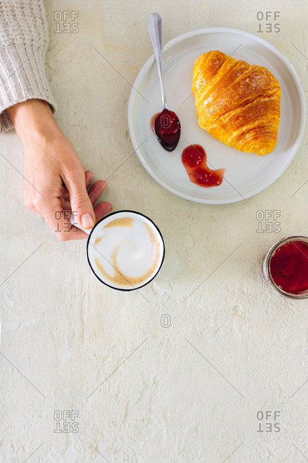 Overhead view of woman with milky coffee, croissant and jam