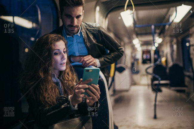 Couple using mobile phone in train, Florence, Italy