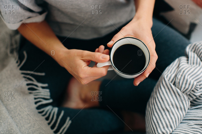 Overhead cropped view of woman holding coffee
