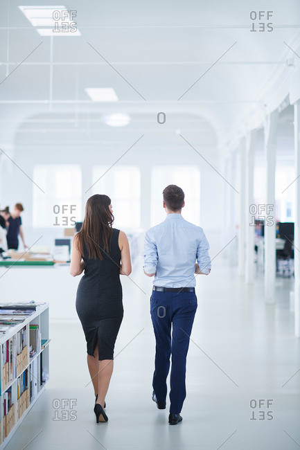 Rear view of colleagues walking through office