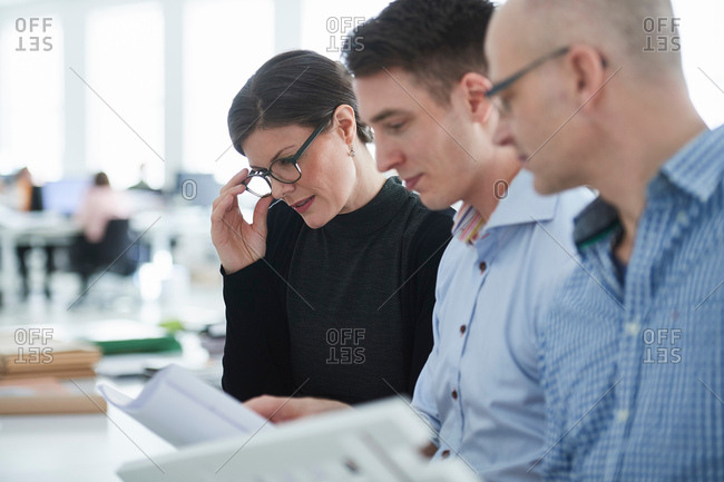 Colleagues in office looking at architectural model