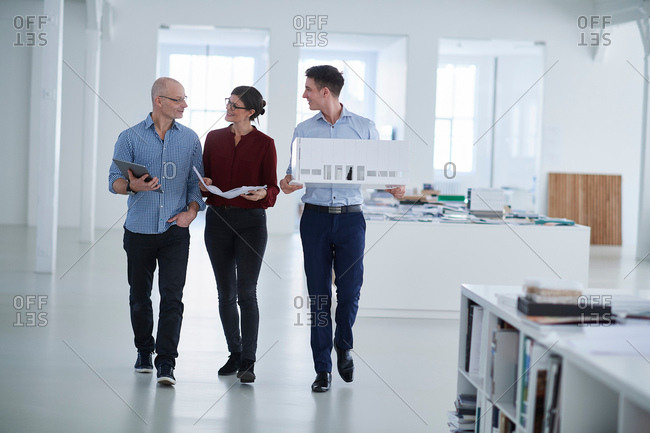 Colleagues walking through open plan office