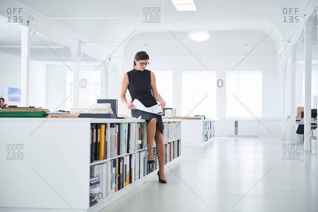 Businesswoman in open plan office looking at paperwork
