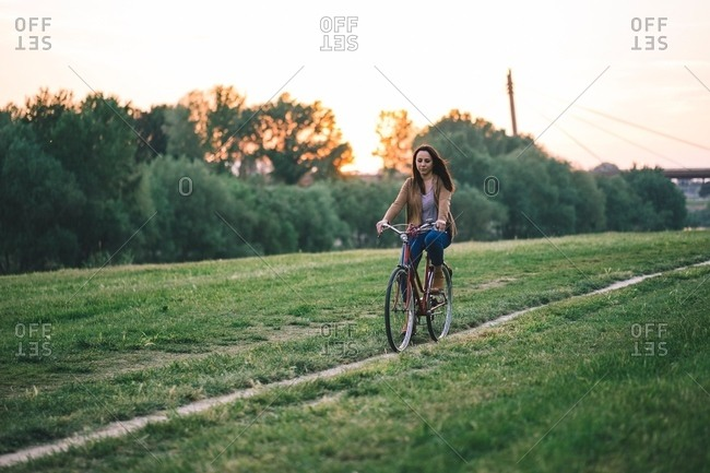 Woman riding bicycle on grass