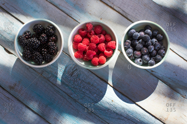 Three bowls containing, blackberries, raspberries and blueberries, overhead view
