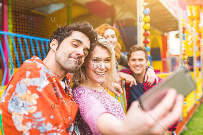 Group of friends at fairground, taking selfie, using smartphone