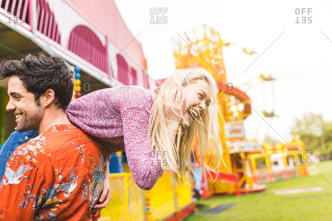 Couple at fairground, man carrying woman over shoulder, laughing
