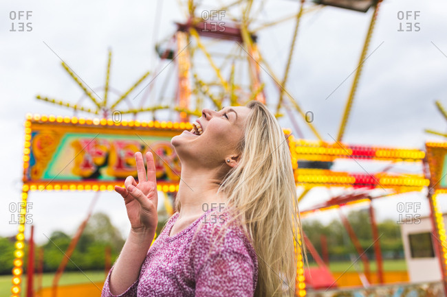 Young woman at fairground, laughing, gesturing with hand