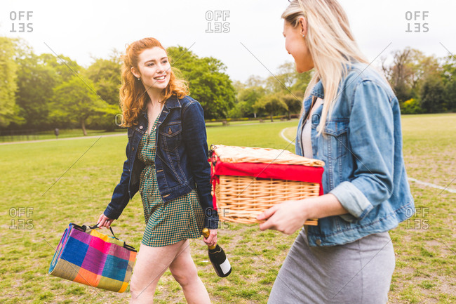 Two women walking across field, carrying picnic basket, blanket and bottle of champagne