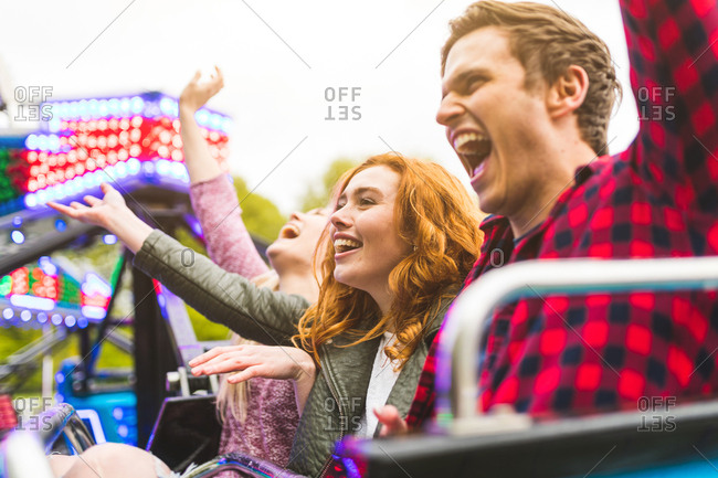 Group of friends on fairground ride, arms raised, laughing