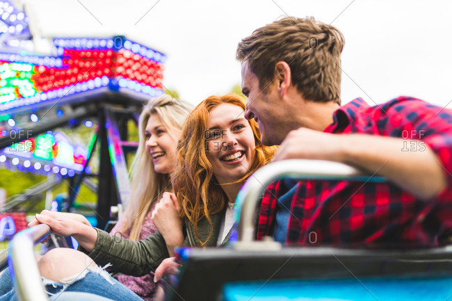 Group of friends on fairground ride, smiling