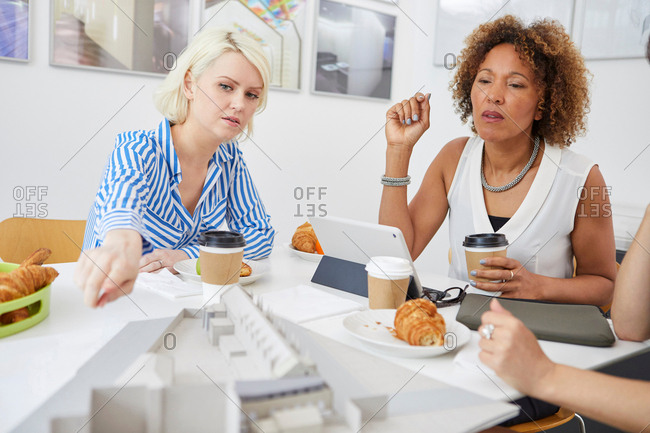 Female architect team pointing at architectural model on table in meeting