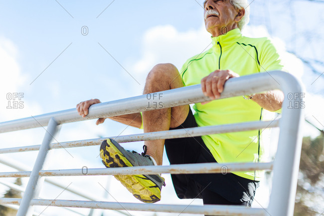 Senior man stretching leg against railings