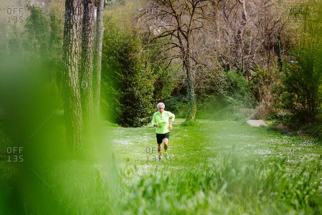 Senior man jogging in gardens