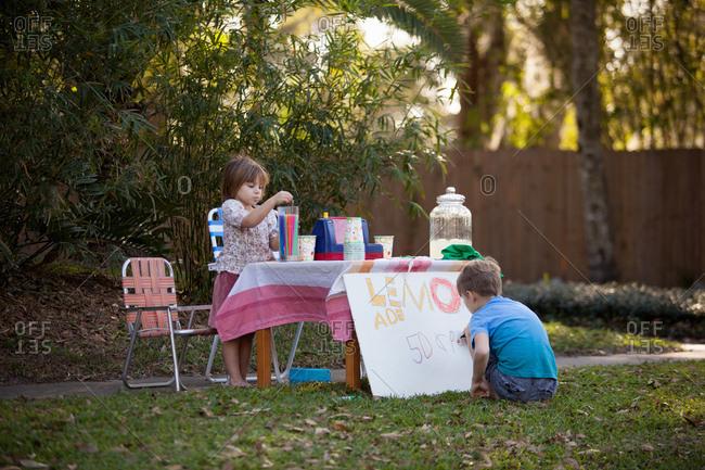 Boy and sister preparing lemonade stand sign in garden