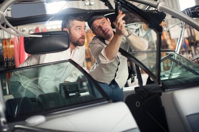Two men checking motor boat in repair workshop