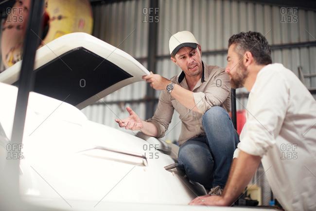 Two men checking boat bodywork in repair workshop