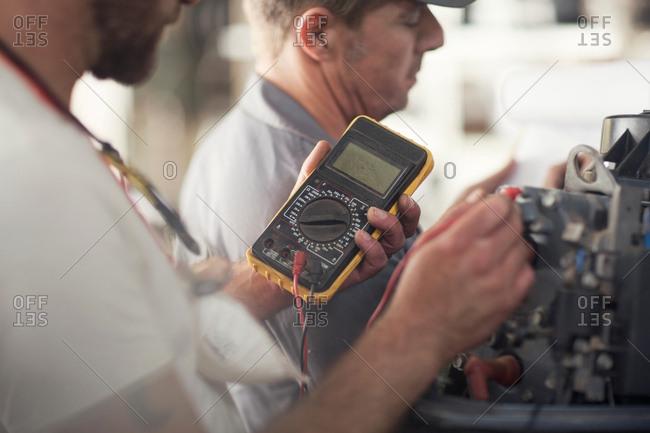 Man using machine to test outboard motor in boat repair workshop
