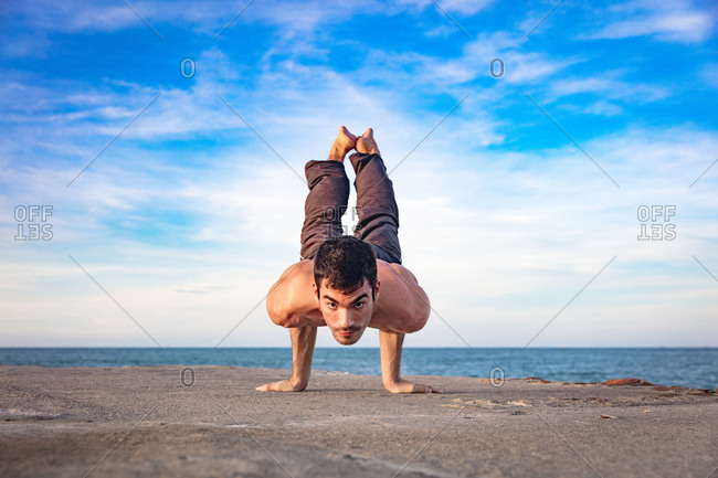 Young man outdoors, in yoga position, balancing on hands