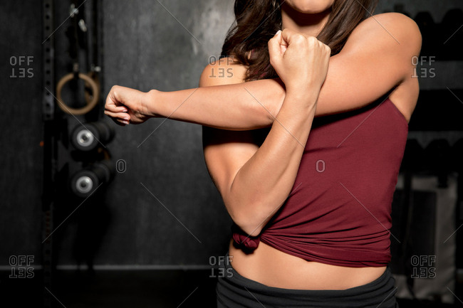 Young woman working out in cross fit gym, mid section