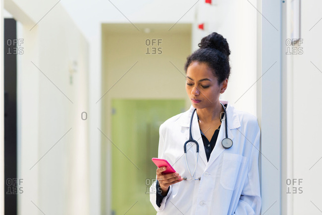 Doctor in hospital looking at mobile phone