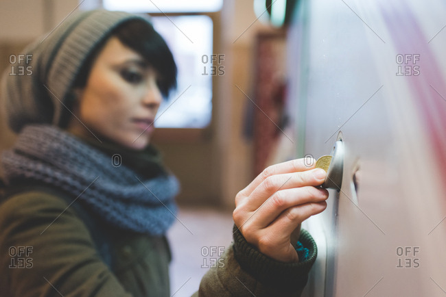 Woman in knit hat inserting coin into railway ticket machine