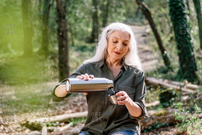 Mature female backpacker pouring drinks flask in forest, Scandicci, Tuscany, Italy
