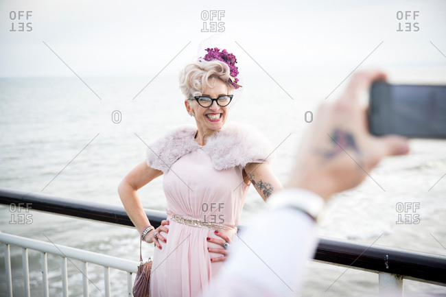 Man taking photograph of 1950's vintage style mature woman on pier on pier