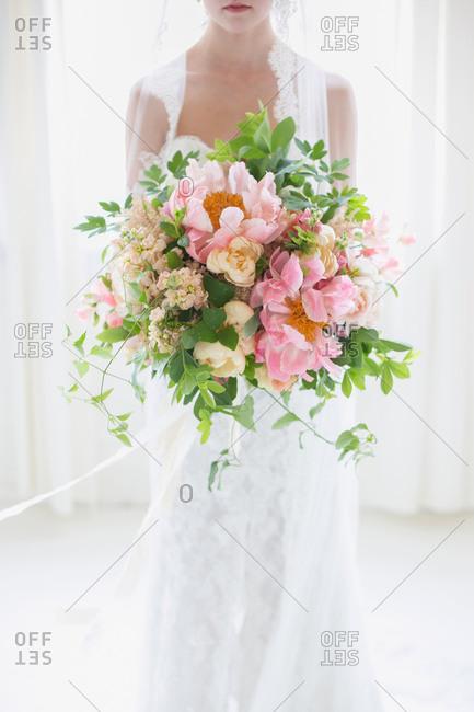 Bride indoors holding oversized bouquet