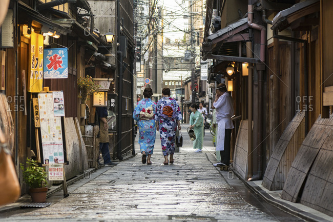 KYOTO, JAPAN - July 19, 2016: Women in traditional kimono walking on narrow lane in Gion district, Kyoto.