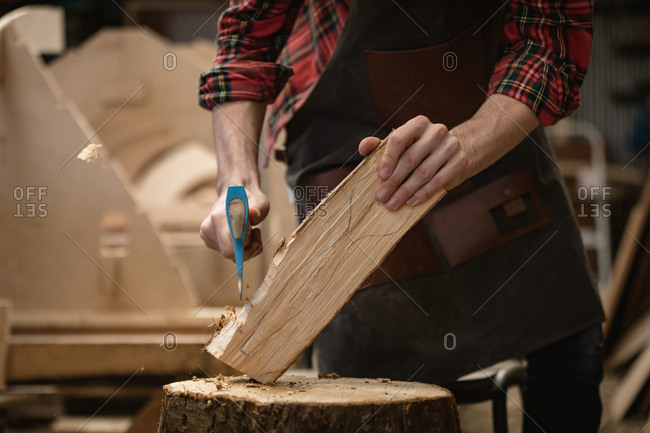 Mid section of carpenter cutting wooden log