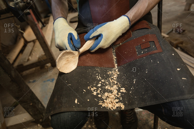 Mid section of carpenter making wooden spoon with worktool