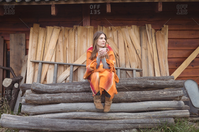 Woman having coffee on log stack