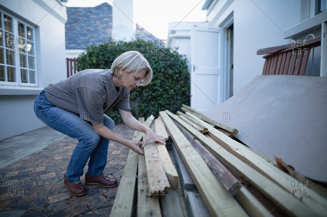 Senior woman carrying wooden planks