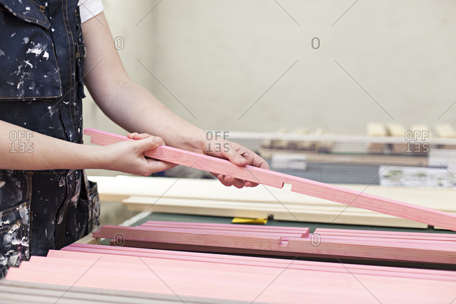 A woman handles wood in a craft workshop