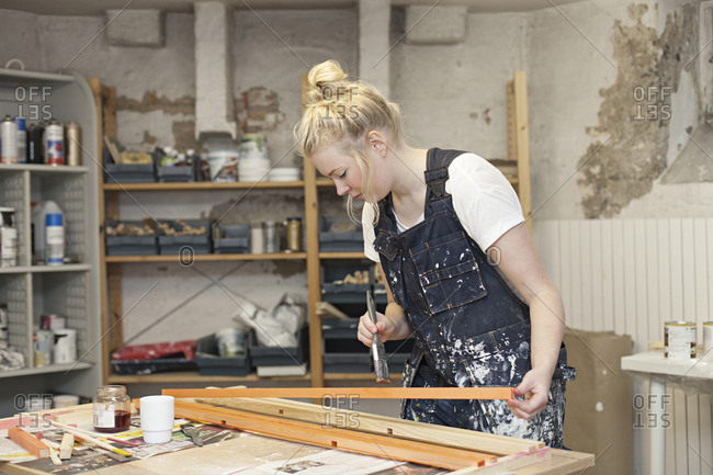 A woman paints wood in a craft workshop