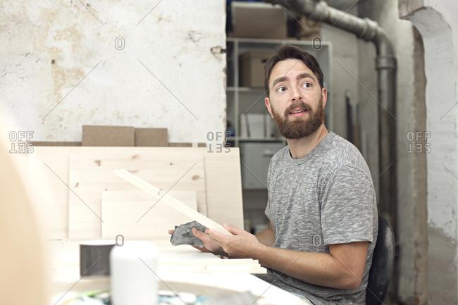 A man sands wood in a craft workshop