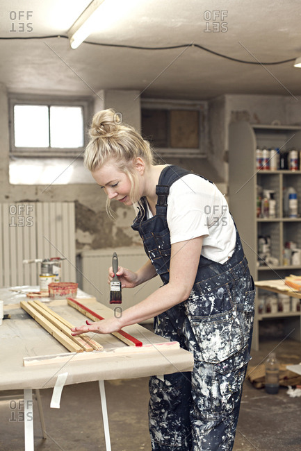 A woman paints wood in her craft studio