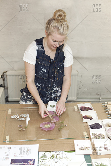 A woman arranges dried flowers on glass