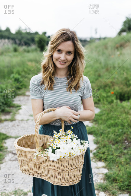 Woman holding basket of flowers in Italian countryside