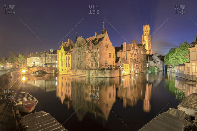 Bruges, Belgium - April 11, 2017: The medieval City Centre, UNESCO World Heritage Site, framed by Rozenhoedkaai canal at night, West Flanders