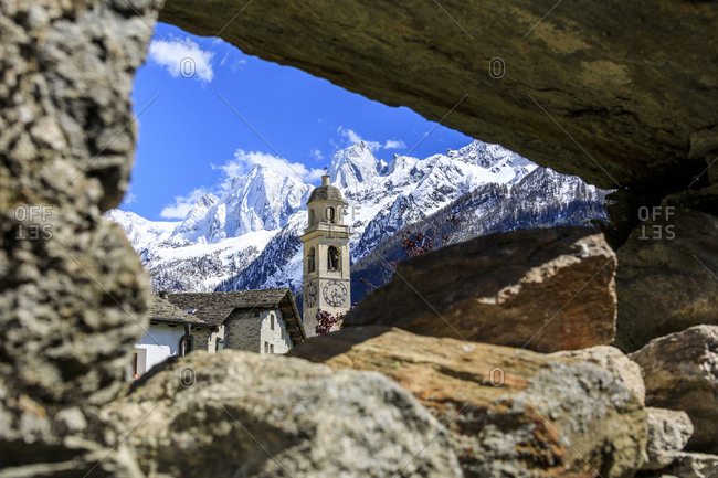 Bell tower and snowy peaks seen from stone arch, Soglio, Maloja, Bregaglia Valley, Engadine, canton of Graubunden, Switzerland Europe